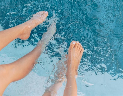 People relax with their foot in a very clean pool that receives regular pool care maintenance in Daytona Florida.