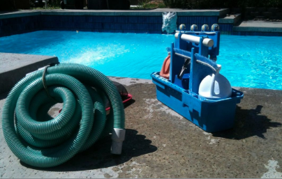 Pool vacuum components and pool service materials and chemicals sit on the edge of the pool deck.