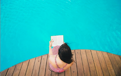 A woman sits and reads on the edge of a pool.